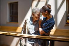 A healthcare worker embracing a happy senior woman