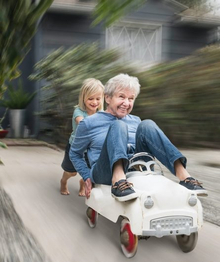 A grandchild pushing her grandmother down the driveway in a toy car